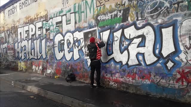 Фанат «Спартака» заклеивает букву Д на стене Цоя